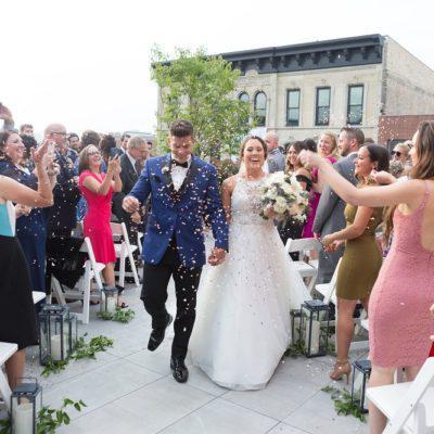 """米歇尔和凯文在芝加哥露西亚阁楼的屋顶上说了""""我愿意""""后,在欢呼声和五彩纸屑的陪伴下走上红毯."""