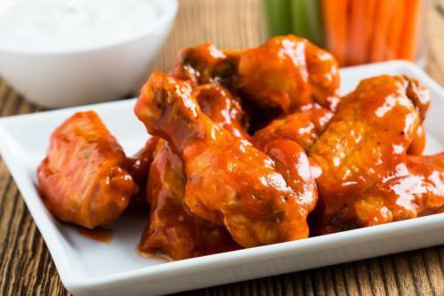 鸡翅堆在白色方形盘子上,涂上水牛酱
