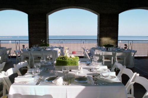 桌子上摆着白色的床单和椅子,背景是海滩和密歇根湖的景色
