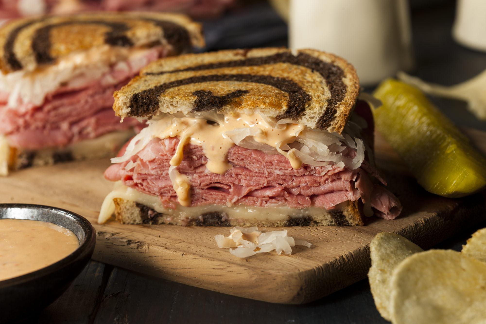 鲁本三明治配大理石黑麦面包, 咸牛肉, 瑞士硬干酪, 泡菜, 还有千岛酱汁. 照片背景是薯条和泡菜.