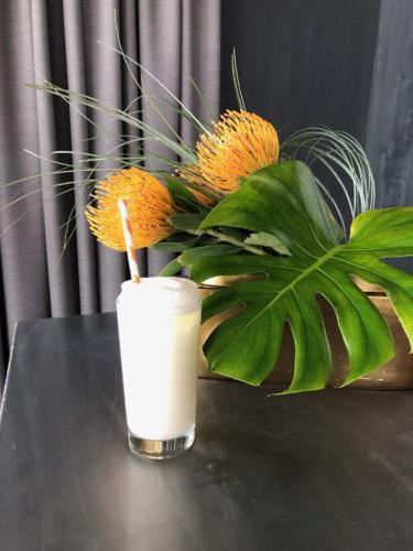 高而透明的玻璃杯,配以淡黄色的鸡尾酒,白色泡沫装饰,黄色和白色的纸吸管