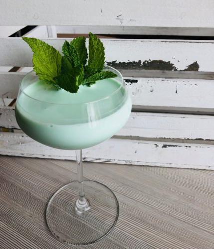 薄荷绿鸡尾酒,配以新鲜薄荷装饰, 设置在一个有纹理的灰色表面与白色水洗, 木板的背景.
